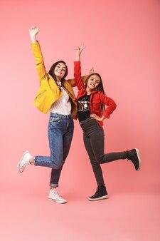 Volle lengte foto van lachende meisjes in casual staande samen, geïsoleerd over rode muur