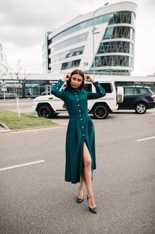Volle lengte foto van mooie brunette jonge dame in groene jurk staande op straat met modern gebouw op de achtergrond