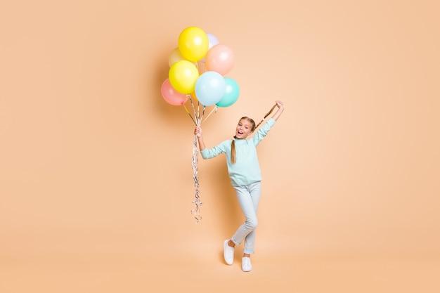 Volle lengte foto van mooie kleine dame veel lucht ballonnen opstaan lange vlecht groet beste vriend klasgenoot dragen blauwe trui jeans sneakers geïsoleerde beige pastelkleur muur