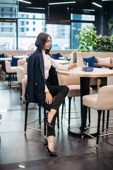 Volle lengte foto van mooie modieuze vrouw zitten in café en genieten van kopje koffie.