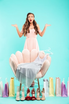 Volle lengte foto van perplex vrouw 20s in jurk winkelen en aarzelen terwijl poseren met veel goederen, geïsoleerd over blauwe muur