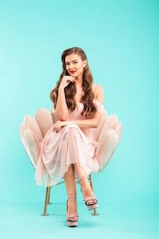 Volle lengte foto van prachtige vrouw 20s in roze jurk zittend in zachte fauteuil met gekruiste benen en haar kin aanraken, geïsoleerd over blauwe muur