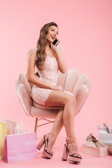 Volle lengte foto van shopper vrouw in jurk met aangenaam mobiel gesprek zittend in fauteuil met boodschappentassen en schoenen, geïsoleerd over roze muur