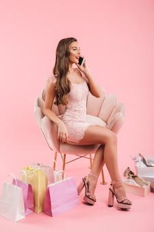 Volle lengte foto van shopper vrouw in jurk praten op mobiele telefoon zittend in fauteuil met boodschappentassen en schoenen, geïsoleerd over roze muur