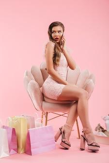 Volle lengte foto van shopper vrouw in jurk spreken op smartphone zittend in fauteuil met boodschappentassen en schoenen, geïsoleerd over roze muur