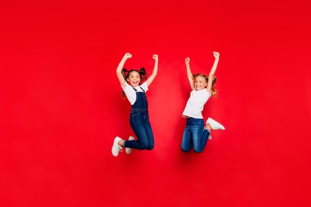 Volle lengte foto van twee extatische bruinblonde vriendinnen met staarten springen winnen kerstloterij vuisten heffen schreeuwen ja draag wit t-shirt outfit geïsoleerde rode kleur achtergrond
