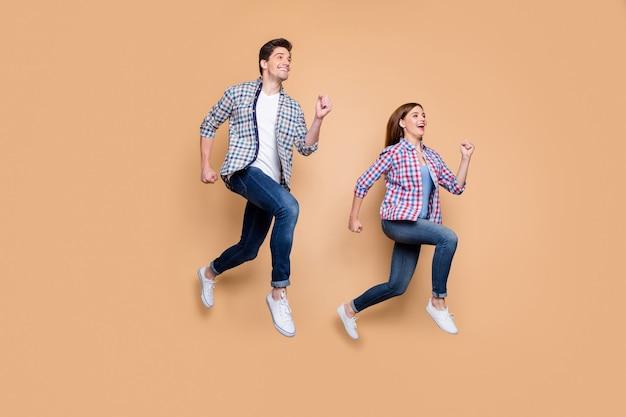 Volle lengte foto van twee mensen dame man springen hoge haasten korting winkelen toeristen reizen beste emoties dragen casual kleding geïsoleerde beige achtergrond