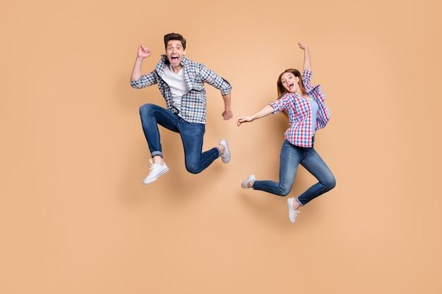 Volle lengte foto van twee mensen gekke dame kerel springen hoog dolblij humeur vieren verkoop winkelen prijzen zwarte vrijdag dragen vrijetijdskleding geïsoleerde beige kleur achtergrond