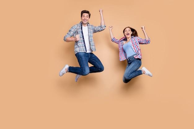 Volle lengte foto van twee mensen gekke dame kerel springen hoog vieren beste overwinning verhogen vuisten opgewonden dragen casual geruite jeans kleding geïsoleerde beige achtergrond