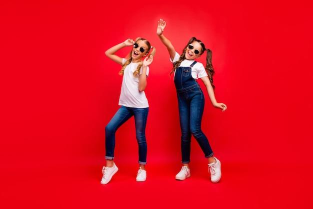 Volle lengte foto van twee mooie kleine dames lange staarten die zich verheugen op schoolfeest beste vrienden dragen coole zon specs jeans overall wit t-shirt geïsoleerde rode felle kleur achtergrond