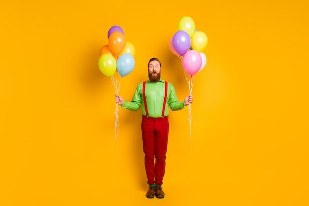 Volle lengte foto van verbaasd imposante charmante man hipster go party houdt veel baloons onder de indruk feestelijke gebeurtenis schreeuw wow omg draag stijlvolle kleding geïsoleerd over gele kleur