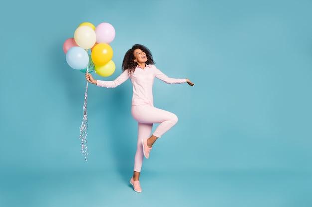 Volle lengte foto van verbazingwekkende golvende donkere huid dame met veel luchtballonnen opgewonden positieve feeststemming draag roze shirt broek geïsoleerde blauwe kleur achtergrond