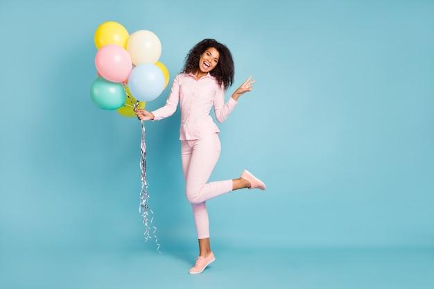 Volle lengte foto van verbazingwekkende golvende donkere huid model dame met veel luchtballonnen met v-teken symbool goed humeur dragen roze overhemd broek geïsoleerde blauwe kleur achtergrond