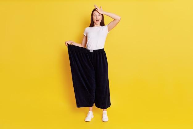 Volle lengte foto van verrast vrouw kleedt enorme broek, kijkend naar de camera met een schokkende uitdrukking en raakt haar hoofd aan met verbazing, geïsoleerd over gele muur.