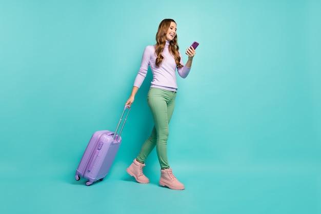 Volle lengte foto van vrolijke dame lopen luchthavenregistratie met rollende koffer browsen telefoon dragen lila trui groene broek schoenen geïsoleerd pastel blauwgroen kleur