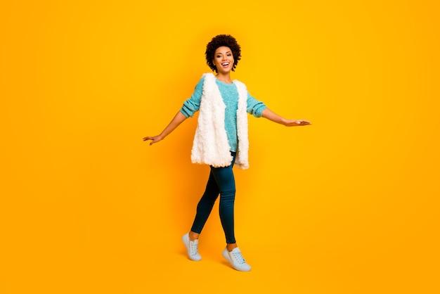 Volle lengte foto van vrolijke droom afro amerikaans meisje veel plezier ontspannen rust gaan wandelen plezier dragen blauwe broek sneakers turkoois trui geïsoleerd over felle kleur muur