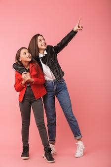Volle lengte foto van vrolijke meisjes in casual staande samen, geïsoleerd over rode muur