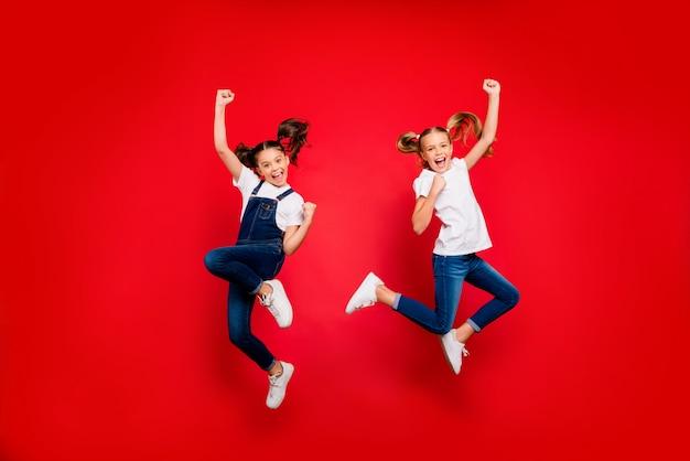 Volle lengte foto van vrolijke twee kleine mensen vriendinnen vieren triomf vuisten heffen schreeuwen ja springen dragen witte t-shirt denim jeans sneakers geïsoleerd felle kleur achtergrond