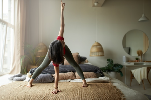 Volle lengte shot van blootsvoets jonge vrouw met flexibel atletisch lichaam staande op tapijt in parivrtta prasarita padottanasana, yoga twist doen, spijsvertering verbeteren, hamstrings en dijen versterken