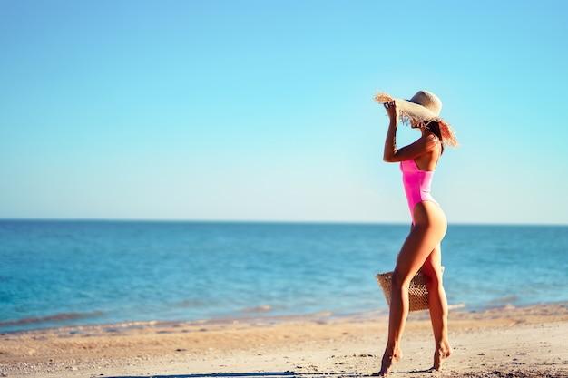 Volle lengte slanke vrouw in roze zwembroek wandelen op oceaan strand zomervakantie ontharingslaser