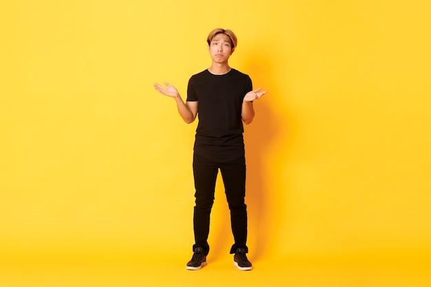 Volle lengte van teleurgestelde en gefrustreerde aziatische kerel die zijn schouders ophaalt en triest kijkt, gele muur.