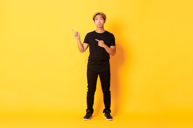 Volle lengte van trieste knappe koreaanse man met blond haar die een boos gezicht maakt, met de vingers in de linkerbovenhoek wijst, het logo met spijt toont, staande gele muur.