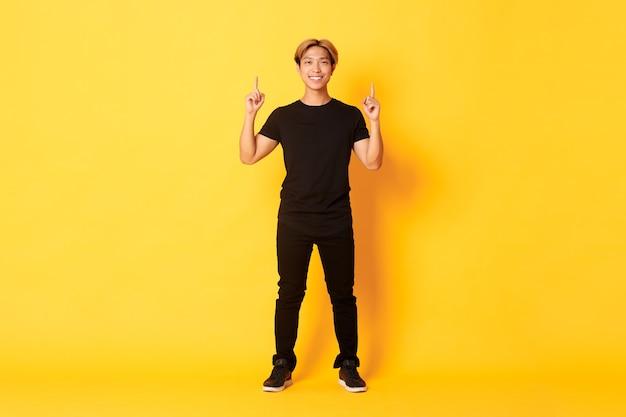 Volle lengte van zelfverzekerde knappe aziatische man met blond haar, glimlachend en wijzende vingers, logo, gele muur tonen.