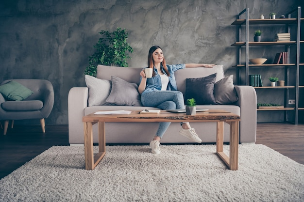 Volle lengte vrij aardig openhartig meisje zit comfortabele divan houd koffie vast