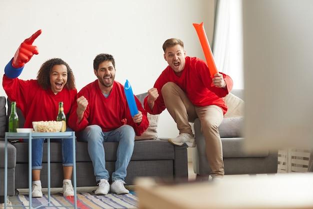 Volle lengte weergave bij groep vrienden kijken naar sportwedstrijd op tv thuis en emotioneel juichen terwijl ze rode teamuniformen dragen
