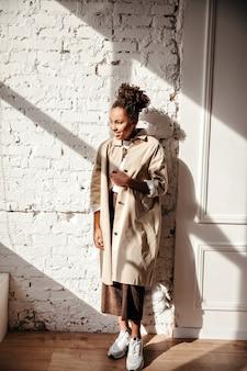 Volle lengte weergave van dromerige vrouw in trenchcoat