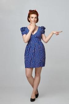 Volle lengte weergave van emotioneel verbaasd jong pin-up model met retro kapsel, elegante schoenen en gestippelde blauwe jurk die een schok uitdrukt, de mond bedekt met de hand en de voorste vingers wijst