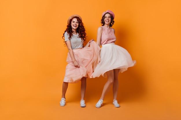 Volle lengte weergave van enthousiaste meisjes met krullend haar dansen met een glimlach. studio shot van blije vriendinnen met plezier op gele achtergrond.