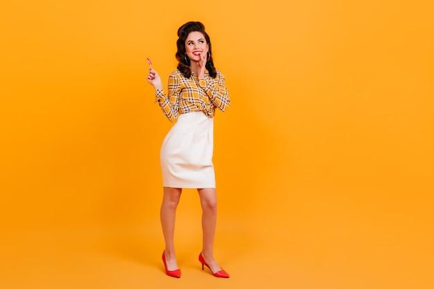 Volle lengte weergave van goed geklede brunette meisje met lolly. studio shot van mooie pinup vrouw poseren op gele achtergrond.