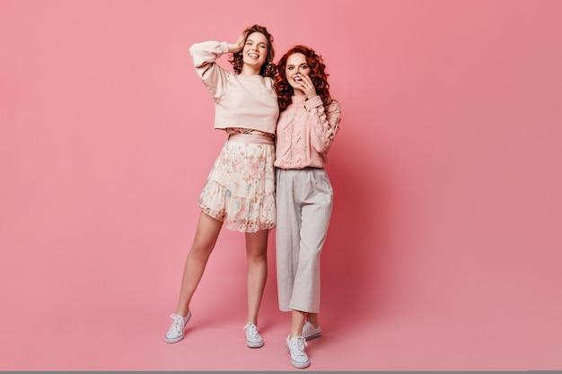 Volle lengte weergave van meisje in rok poseren met vriend. studio die van twee stijlvolle jonge dames is ontsproten die zich op roze achtergrond bevinden.