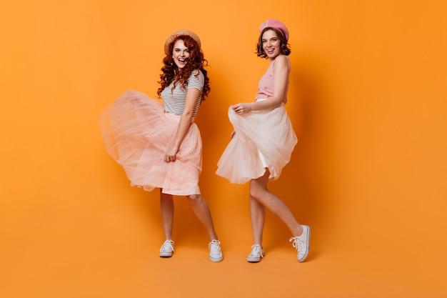 Volle lengte weergave van romantische meisjes in rokken. studio shot van aantrekkelijke krullende vrouwen dansen op gele achtergrond.