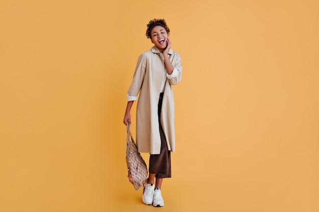 Volle lengte weergave van stijlvolle vrouw met string tas