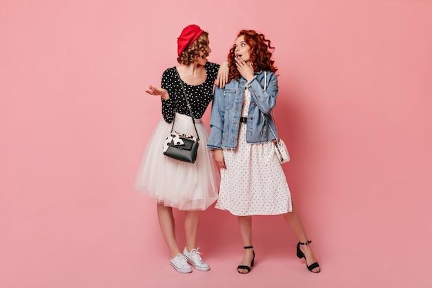 Volle lengte weergave van twee stijlvolle meisjes praten op roze achtergrond. studio die van bevallige dames is ontsproten.