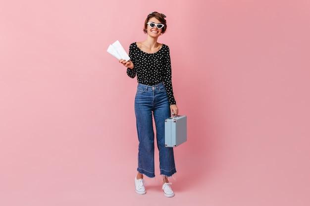 Volle lengte weergave van vrouw in zonnebril met kaartjes