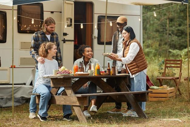 Volle lengte zicht op diverse groep jonge mensen die buiten picknicken tijdens het kamperen met trailer...