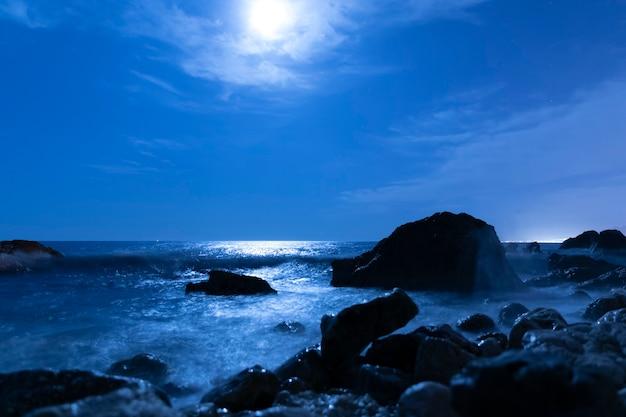Volle maan aan de hemel boven zeewater