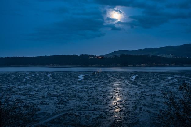 Volle maan, luchten en weerspiegelingen in de monding van de eo