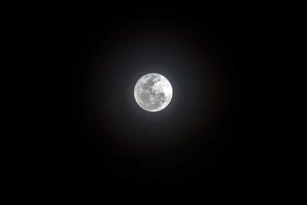 Volle maan met heldere halo in de donkere hemel