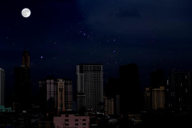 Volle maan met sterrenhemel over de stadsachtergrond