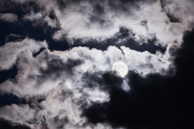 Volle maan over de wolken aan de nachtelijke hemel