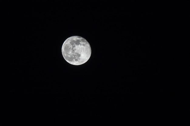 Volle maan over donkere zwarte lucht 's nachts