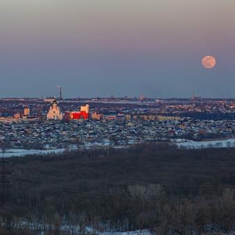 Volle maan stijgt boven de stad. zonsondergangtijd in de schemeringhemel. uitzicht op de orthodoxe kerk.