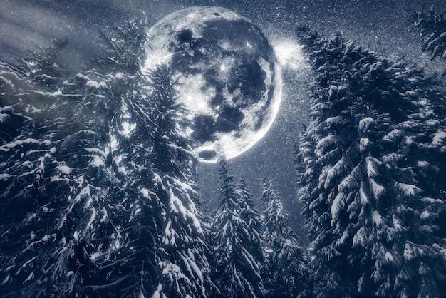 Volle maan stijgt boven de wintervallei bedekt met verse sneeuw. fantastische melkweg in een sterrenhemel. kerstnacht.