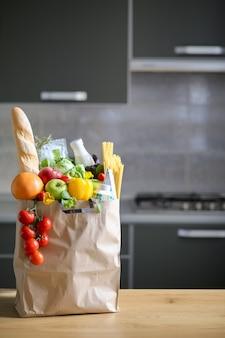 Volle papieren zak met gezond voedsel op de achtergrond van de keuken