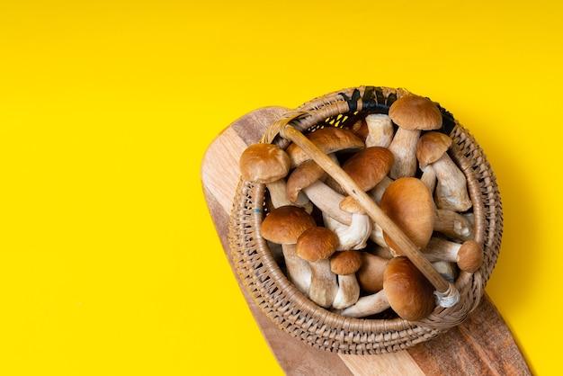 Volle rieten mand met boletus edulis-paddenstoelen op gele achtergrond