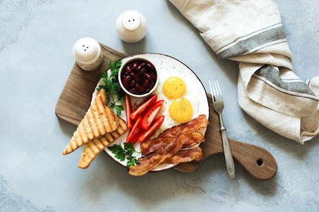 Volledig bak traditioneel engels ontbijt met gebakken eieren, worstjes, spek, bloedworst, bonen, toast en thee op grijze betonnen achtergrond. bovenaanzicht